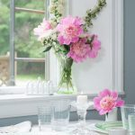 Breakfast Table decorated in white and green service with pink flowers. Overlooking the back yard.
